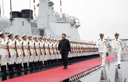 Chinese President Xi Jinping reviews the honor guards of the Chinese People's Liberation Navy before boarding the destroyer Xining for the naval parade celebrating the 70th founding anniversary of the Chinese People's Liberation Army Navy in Qin