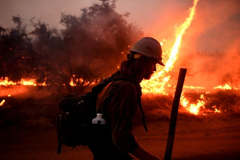 "A firefighter helps to set counter-fires as the El Dorado fire approaches in Yucaipa on Sept. 7. <span class=""copyright"">(Los Angeles Times)</span>"