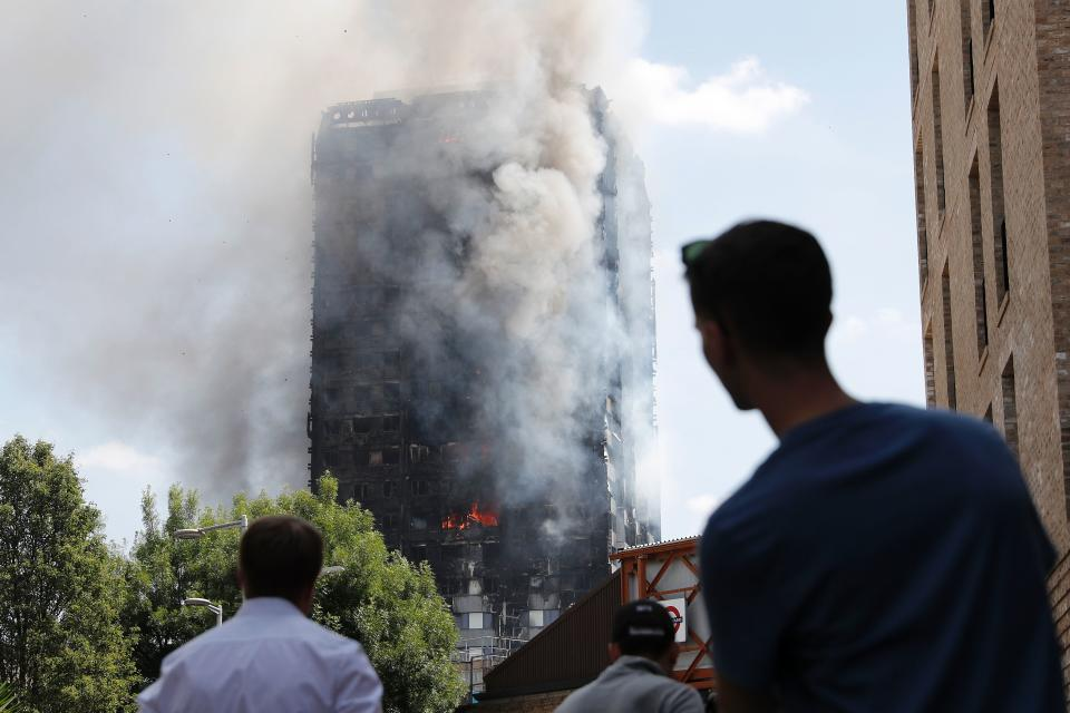 TOPSHOT - Pedestrians look up towards Grenfell Tower, a residential block of flats in west London on June 14, 2017, as firefighters continue to control a fire that engulfed the building in the early hours of the morning. Shaken survivors of a blaze that ravaged a west London tower block told Wednesday of seeing people trapped or jump to their doom as flames raced towards the building's upper floors and smoke filled the corridors.   / AFP PHOTO / Adrian DENNIS        (Photo credit should read ADRIAN DENNIS/AFP via Getty Images)