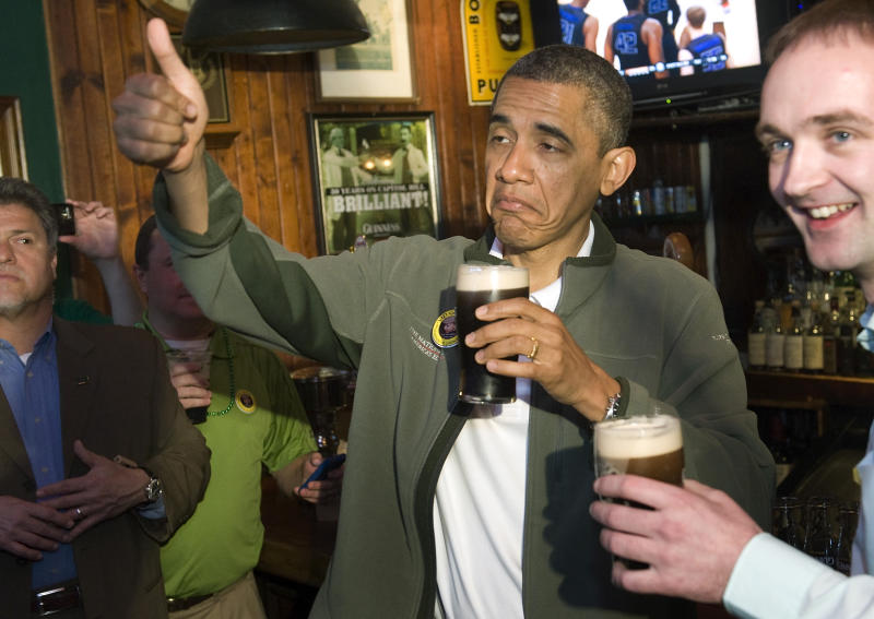 U.S. President Barack Obama (C) gives a thumbs-up as he celebrates St. Patrick's Day with a pint of Guinness during a stop at the Dubliner Irish pub in Washington, March 17, 2012. REUTERS/Jonathan Ernst (UNITED STATES - Tags: POLITICS SOCIETY TPX IMAGES OF THE DAY)