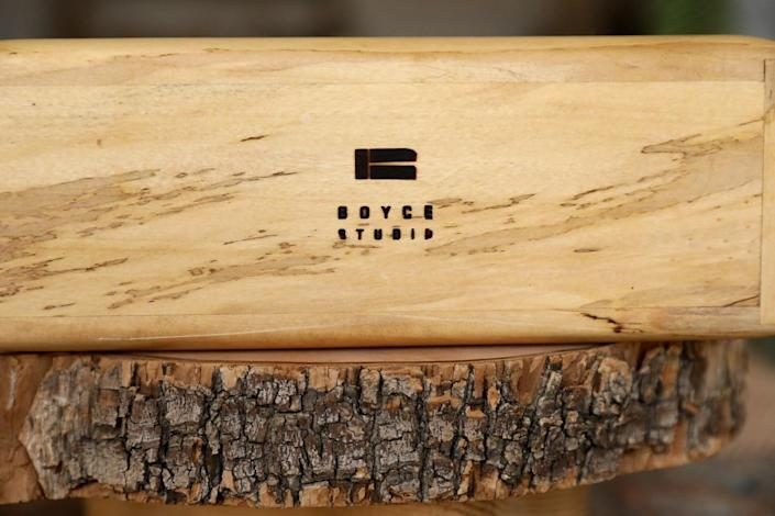 A Boyce Studio stamp in the bottom of a wood urn resting on top of a cross-section of a log.