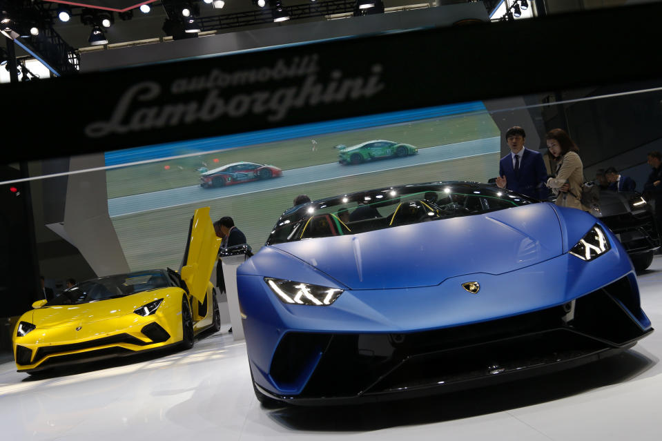 Staff members chats with visitors near the Lamborghini Huracan models on being displayed at the China Auto China in Beijing, Thursday, April 26, 2018. Auto China 2018, the industry's biggest sales event this year, is overshadowed by mounting trade tensions between Beijing and U.S. President Donald Trump, who has threatened to hike tariffs on Chinese goods including automobiles in a dispute over technology policy. (AP Photo/Andy Wong)