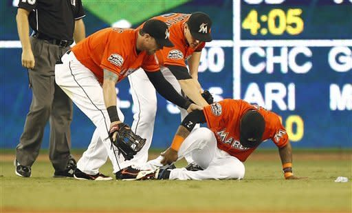 Miami Marlins players Scott Cousins and Logan Morrison (5) check on shortstop Jose Reyes after Reyes and Cousins collided in the outfield during the third inning of an interleague baseball game against the Toronto Blue Jays in Miami, Sunday, June 24, 2012. (AP Photo/J Pat Carter)