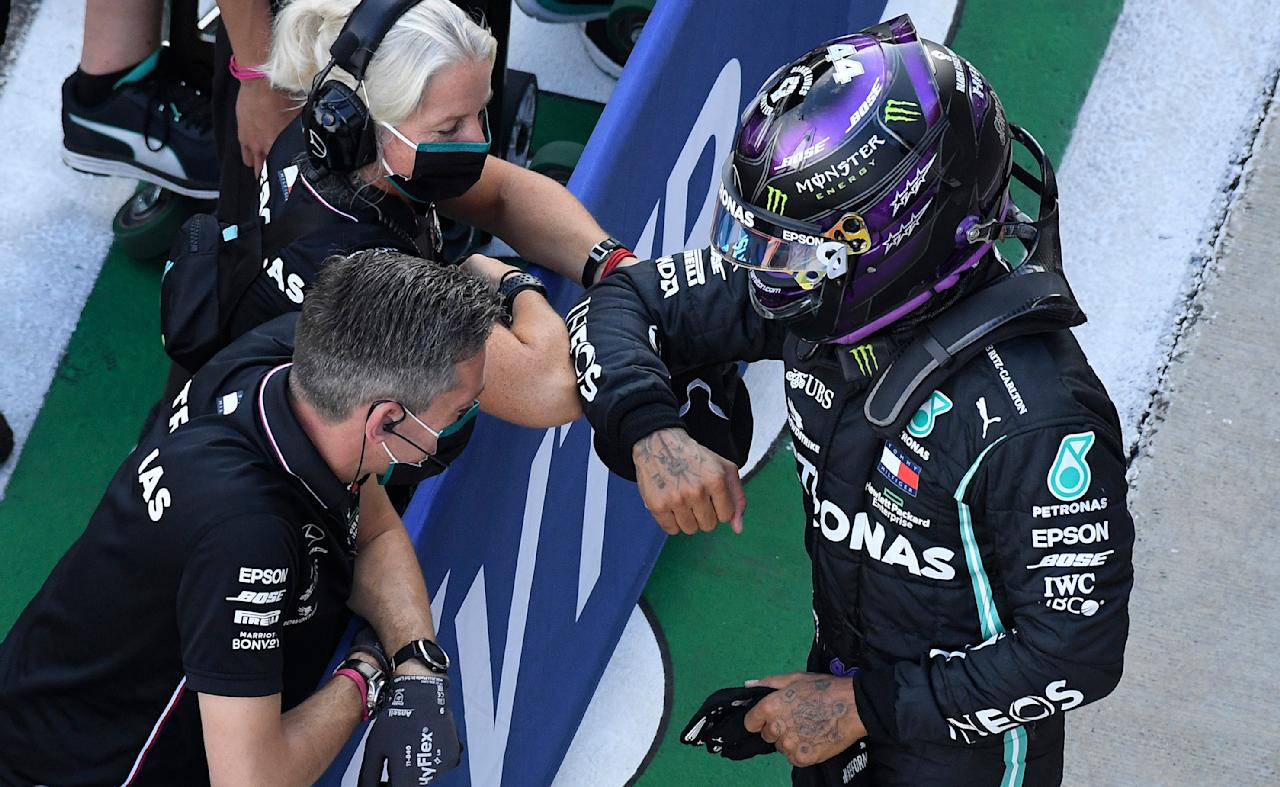 Mercedes driver Lewis Hamilton of Britain, right, celebrates after clocking the fastest time during the qualifying session for the upcoming Russian Formula One Grand Prix, at the Sochi Autodrom circuit, in Sochi, Russia, Saturday, Sept. 26, 2020. The Russian Formula One Grand Prix will take place on Sunday. (Kirill Kudryavtsev, Pool via AP)