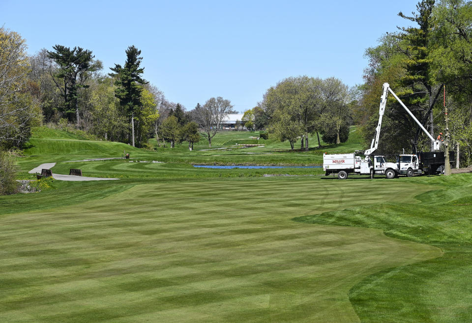 Workers trim trees at a closed Lakeview Golf Course during the COVID-19 pandemic in Mississauga, Ontario, on Wednesday, May 12, 2021. The Ontario government has deemed golf courses and other outdoor recreational sports unsafe to open at this current time. (Nathan Denette/The Canadian Press via AP)