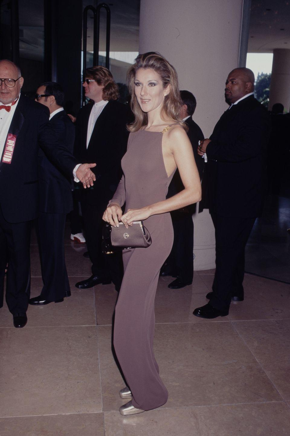 <p>In a nude one-shouldered gown and matching purse at an event. </p>
