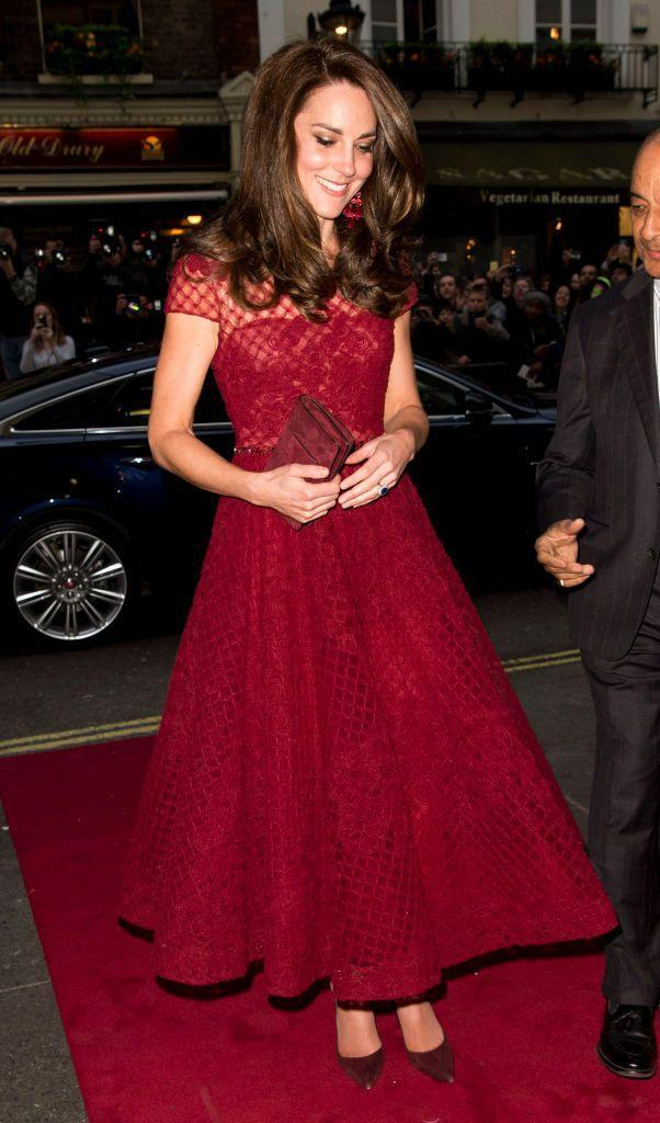 <p>The Duchess of Cambridge enjoyed a night on the town at the Theatre Royal for the West End premiere of <em>42nd Street</em>. The production was affiliated with the East Anglia's Children's Hospice, of which the Duchess is a patron. She arrived in a sheer, crimson Marchesa dress embedded with a subtle gem-lined belt. Her maroon clutch matched her shoes as well as her Oscar de la Renta earrings. </p>