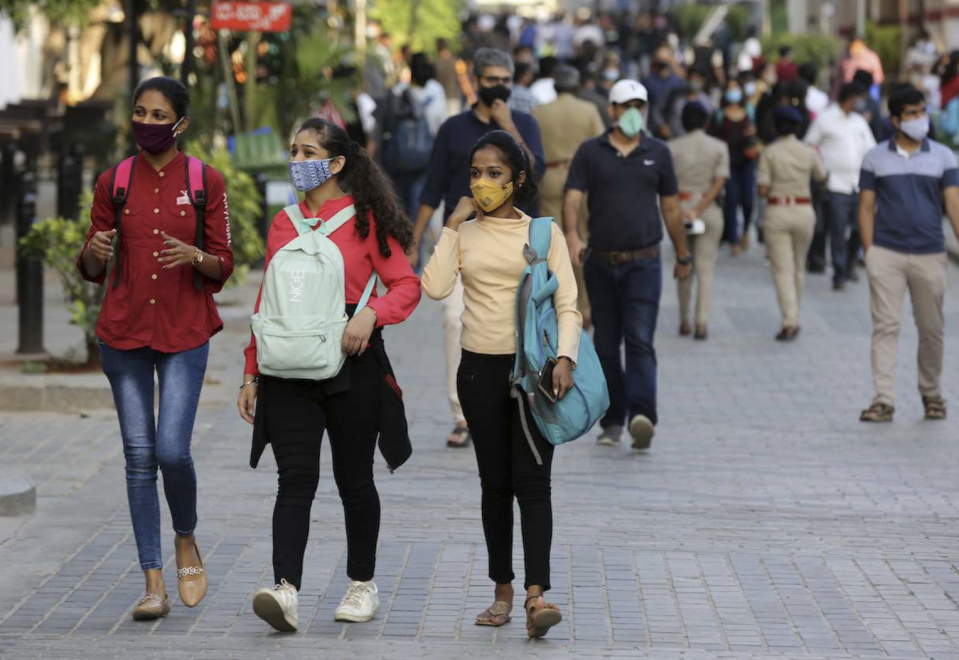 Crowd wearing masks walks through an outdoor area in India.