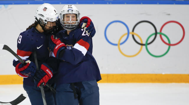 Megan Bozek of the United States, left, congratulates Kacey Bellamy of the United States after Bellamy scored a goal against Sweden during the first period of the 2014 Winter Olympics women's semifinal ice hockey game at Shayba Arena Monday, Feb. 17, 2014, in Sochi, Russia. (AP Photo/Julio Cortez)