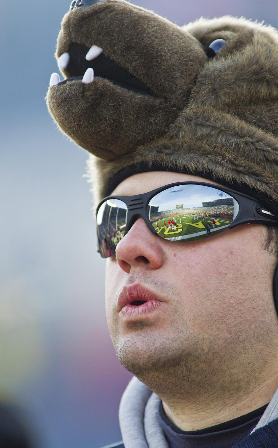 Michigan alum Vincent Coughlin from Chicago, wears a wolverine headgear in the Michigan Stadium stands before an NCAA college football game against Ohio State in Ann Arbor, Mich., Saturday, Nov. 30, 2013. (AP Photo/Tony Ding)