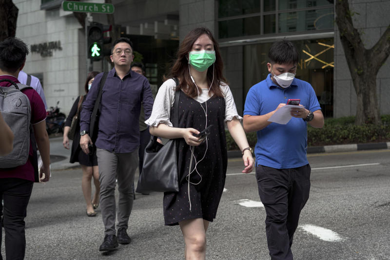 SINGAPORE, SINGAPORE - FEBRUARY 28: People wearing masks cross a traffic junction at the Central Business District on February 28, 2020 in Singapore. The coronavirus, originating in Wuhan, China has spread to over 80,000 people globally, more than 50 countries have now been infected. (Photo by Ore Huiying/Getty Images)