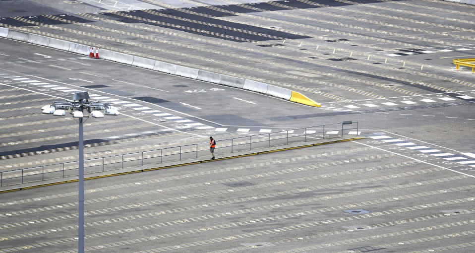 A man walks through empty passenger lanes at the Port of Dover, south east England, Friday March 20, 2020. For most people, the new coronavirus causes only mild or moderate symptoms, such as fever and cough. For some, especially older adults and people with existing health problems, it can cause more severe illness, including pneumonia. (Gareth Fuller/PA via AP)