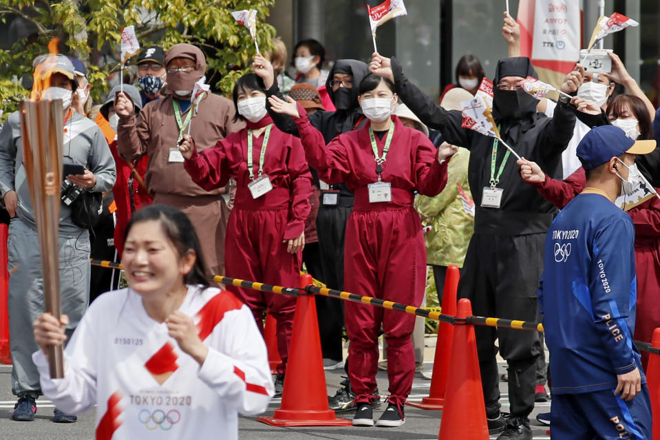 Spectators wearing face masks and ninja outfits, cheer a torchbearer carrying the Olympic torch in Iga, Mie prefecture, central Japan, Thursday, April 8, 2021. Tokyo, the capital of Japan, has asked the central government for permission to implement emergency measures to curb a surge in a rapidly spreading and more contagious coronavirus variant, just over three months before the start of the Olympics. (Kyodo News via AP)