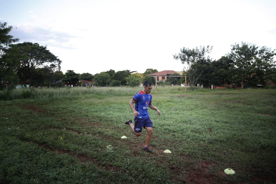 """Defender Jose """"Ruli"""" Rios, of the Fulgencio Yegros Club, second division, runs during a solitary, early morning training session, in Ypane, Paraguay, Saturday, Jan. 30, 2021. A professional since age 18, the 35-year-old defender helped four clubs reach Paraguay's first division. To survive during during the COVID-19 pandemic, Rios is working as a gardener as he waits for the 2021 season to begin. (AP Photo/Jorge Saenz)"""