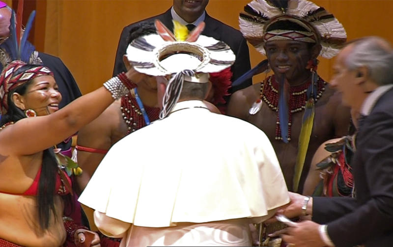 In this frame grab from video, a woman helps Pope Francis adjust an feathered hat given to him by representatives of one of Brazil's native tribes during a meeting at the Municipal Theater in Rio de Janeiro, Brazil, Saturday, July 27, 2013. Pope Francis is on the sixth day of his trip to Brazil where he will attend the 2013 World Youth Day in Rio. (AP Photo/TV Pool)