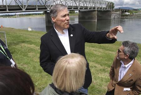 Washington State Governor Inslee looks over the scene as a span of highway bridge sits in the Skagit River
