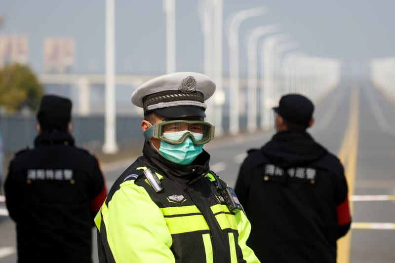 A police officer wears a face mask and goggles at a checkpoint at the Jiujiang Yangtze River Bridge