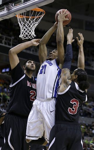 Saint Louis forward Dwayne Evans (21) shoots in between New Mexico State center Sim Bhullar (2) and forward Remi Barry (3) during the first half of a second-round game in the NCAA college basketball tournament in San Jose, Calif., Thursday, March 21, 2013. (AP Photo/Ben Margot)
