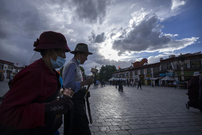 Members of the Tibetan Buddhist faithful spin prayer wheels as they circumambulate around the Jokhang Temple in Lhasa in western China's Tibet Autonomous Region, as seen during a rare government-led tour of the region for foreign journalists, Tuesday, June 1, 2021. Long defined by its Buddhist culture, Tibet is facing a push for assimilation and political orthodoxy under China's ruling Communist Party. (AP Photo/Mark Schiefelbein)