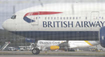 Seen though a perimeter fence a British Airways aircraft takes off past a Thomas Cook plane in the background at Gatwick Airport, England, Monday, Sept. 23, 2019. British tour company Thomas Cook collapsed early Monday after failing to secure emergency funding, leaving tens of thousands of vacationers stranded abroad. (AP Photo/Alastair Grant)