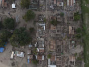 The shells of homes lay in ruins in La Samaritana village after last year's hurricanes Eta and Iota destroyed the area in La Lima, on the outskirts of San Pedro Sula, Honduras, Wednesday, Jan. 13, 2021. Those who lived here are now in nearby temporary shacks made of wood and zink sheets. (AP Photo/Moises Castillo)