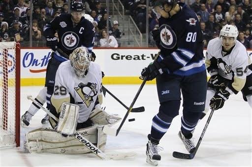 Pittsburgh Penguins goaltender Marc-Andre Fleury (29) stops Winnipeg Jets forward Nik Antropov's (80) shot during second-period NHL hockey game action in Winnipeg, Manitoba, Friday, Dec. 23, 2011. (AP Photo/The Canadian Press, John Woods)