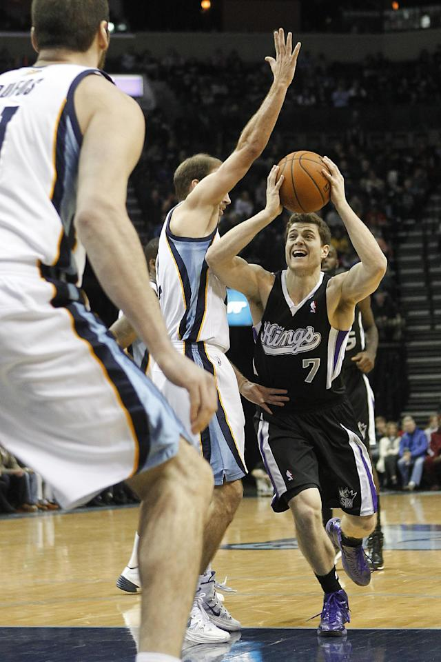 Sacramento Kings guard Jimmer Fredette (7) drives to the basket against Memphis Grizzlies guard Nick Calathes, center, and center Kosta Koufos, left, in the first half of an NBA basketball game on Friday, Jan. 17, 2014, in Memphis, Tenn. (AP Photo/Lance Murphey)