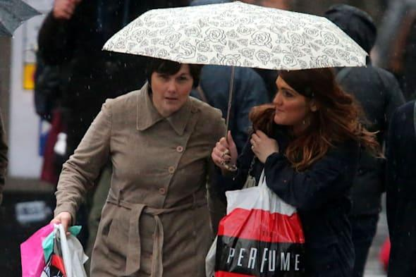 File photo dated 22/12/12 of shoppers brave the wind and rain. Britain's under-pressure high streets suffered a washout last month as monthly retail sales fell for the first time in nearly a year. PRESS ASSOCIATION Photo. Issue date: Tuesday March 11, 2014. Like-for-like sales dropped by 1% in February compared to the same period in 2013, as poor weather took its toll on town centre stores, according to figures from the British Retail Consortium (BRC) and KPMG. Web commerce continued to gather pace, with online non-food sales up 14.3%. But the impact of discount supermarkets such as Aldi and Lidl helped drag down the overall figure. See PA story ECONOMY Retail. Photo credit should read: Andrew Milligan/PA Wire