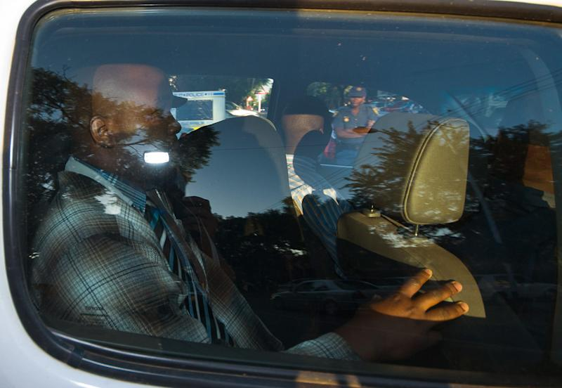 Olympian Oscar Pistorius, center with head covered, leaves the Brooklyn Police Station in a police vehicle in Pretoria, South Africa, Tuesday, Feb. 19, 2013, en route to the magistrates court for a bail hearing. Pistorius arrived early at the courthouse for a bail hearing where his lawyers and police expect to reveal details of the alleged killing of his model girlfriend. (AP Photo/ Waldo Swiegers)