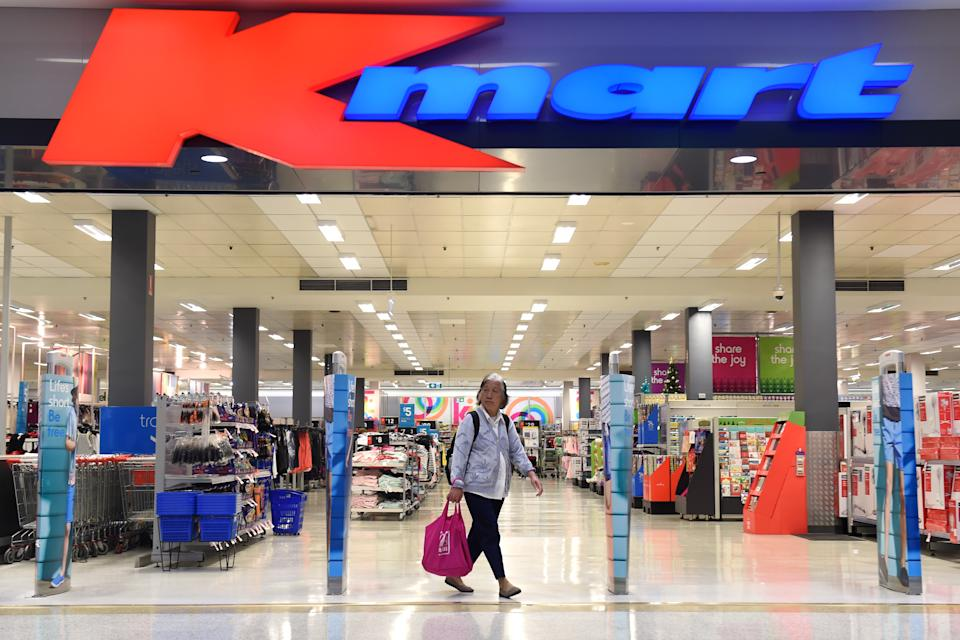 Picture of a Kmart store, with a customer exiting the store.