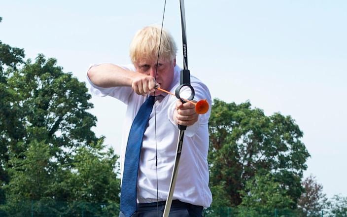 Boris Johnson takes aim on a visit to a school in Upminster, Essex - Lucy Young/Evening Standard/PA
