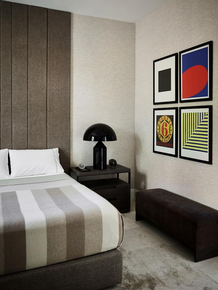 """<div class=""""caption""""> There are two guest bedrooms on the main floor of the home. This one, like the master bedroom, also features a custom headboard and linens by <a href=""""https://www.matouk.com/"""" rel=""""nofollow noopener"""" target=""""_blank"""" data-ylk=""""slk:Matouk"""" class=""""link rapid-noclick-resp"""">Matouk</a>. Pops of color are provided by the quartet of Robert Indiana prints, and texture is added by the <a href=""""https://www.phillipjeffries.com/"""" rel=""""nofollow noopener"""" target=""""_blank"""" data-ylk=""""slk:Phillip Jeffries"""" class=""""link rapid-noclick-resp"""">Phillip Jeffries</a> wall covering and the custom carpet by <a href=""""https://artandloom.com/"""" rel=""""nofollow noopener"""" target=""""_blank"""" data-ylk=""""slk:Art and Loom"""" class=""""link rapid-noclick-resp"""">Art and Loom</a>. </div>"""
