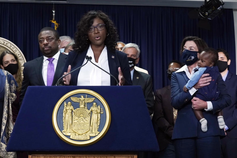 """New York state Assembly member Phara Souffrant Forrest speaks, as New York Gov. Kathy Hochul, right, holds her son David, before Hochul signed the """"Less is More"""" law, during ceremonies in the governor's office, in New York, Friday, Sept. 17, 2021. New Yorkers will be able to avoid jail time for most nonviolent parole violations under a new law that will take effect in March, and largely eliminates New York's practice of incarcerating people for technical parole violations. At left is Lt. Gov. Brian Benjamin. (AP Photo/Richard Drew)"""