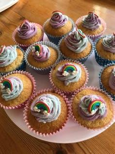 A plate of cupcakes decorated with rainbows.