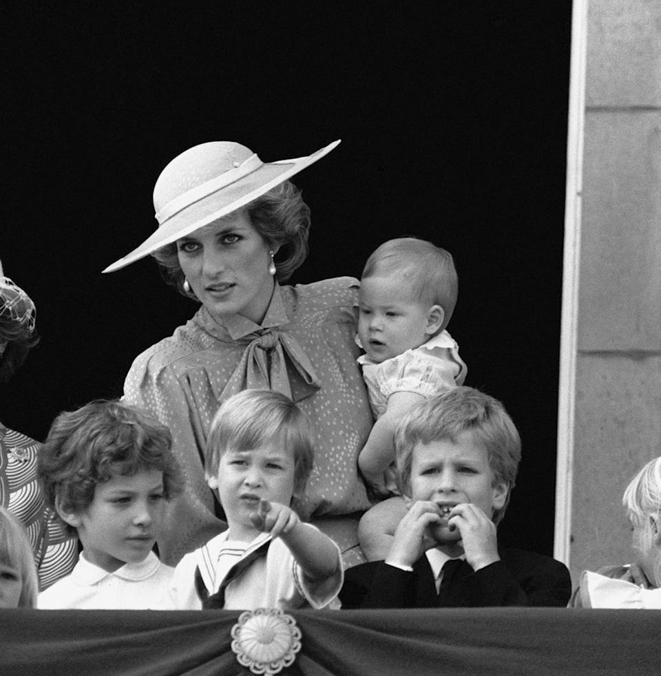 Princess Diana holds baby Prince Harry, as Lord Frederick Windsor, Prince William and Peter Phillips watch on. (PA Images)