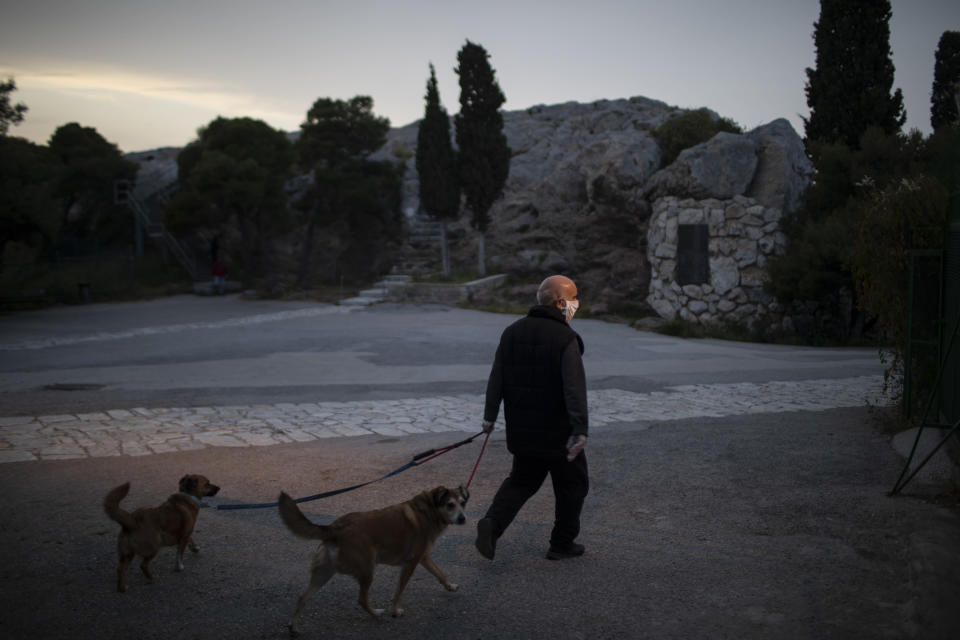 An elderly man wearing a mask to protect against the spread of the coronavirus walks with his dogs near Areopagus hill during a lockdown by the Greek government to prevent the spread of COVID-19, in Athens, on Tuesday, April 21, 2020. Most of Athens' historic center, Plaka and nearby districts in a semi-circle around the Acropolis, is unusually quiet during the two nationwide lockdowns imposed by the greek goverment.(AP Photo/Petros Giannakouris)