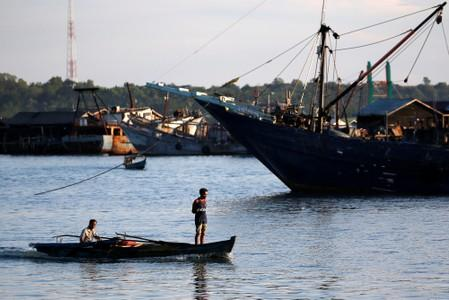 A man stands as he travels on a wooden boat near a port in Tanjungpinang, on the island of Bintan