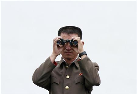 A North Korean soldier looks through binoculars, near the North Korean town of Sinuiju