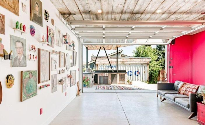 A large garage door in the shipping container's opens up to a gorgeous wooden outdoor patio.