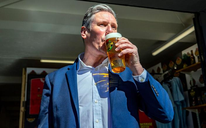 Sir Keir Starmer drinks a pint during a visit to Wrexham Lager Brewery - PA