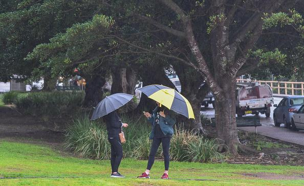 Two young women have a conversation together underneath umbrellas during rain at Bradfield Park in Sydney, Australia.