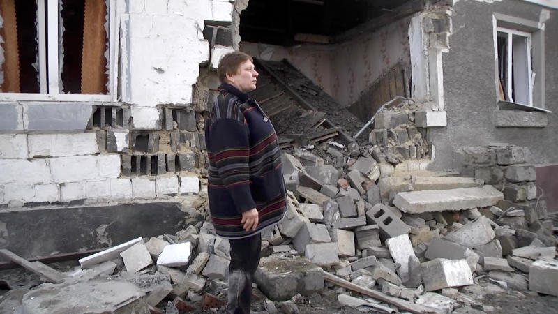 In this video grab provided by the RU-RTR Russian television, a woman stands next to her home, that was distroyed during cross fire between Russia-backed separatists and Ukrainian forces, in Zaitseve, Donetsk region, eastern Ukraine, Tuesday, Feb. 18, 2020.  Ukraine and Russia-backed separatists blamed each other for an outbreak of fighting in the country's rebel-held east on Tuesday. (RU-RTR Russian Television via AP)