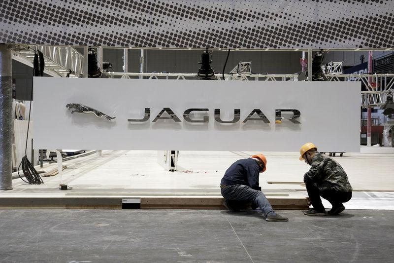 Workers set up a Jaguar booth inside the National Exhibition and Convention Center, the venue for the upcoming China International Import Expo, in Shanghai