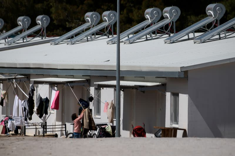 A migrant hangs a blanket to dry in the Ritsona camp after authorities found 20 coronavirus cases and placed the camp under quarantine, following the outbreak of coronavirus disease (COVID-19), in Ritsona