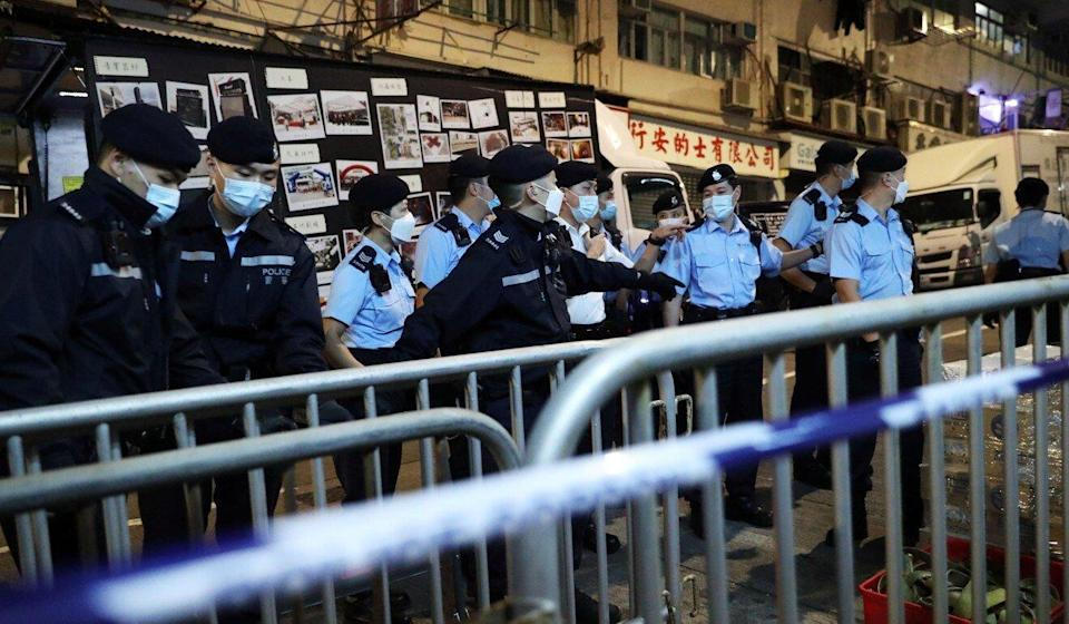 Police officers set up barriers for the lockdown of blocks A to D of Tung Fat Building. Photo: Edmond So