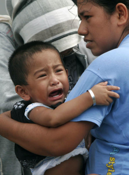 A boy cries as he is carried by his mother as they evacuate to higher ground after a strong earthquake was felt in Banda Aceh, Aceh province, Sumatra island, Indonesia, Wednesday, April 11, 2012. Two massive earthquakes triggered back-to-back tsunami warnings for Indonesia on Wednesday, sending panicked residents fleeing to high ground in cars and on the backs of motorcycles. There were no signs of deadly waves, however, or serious damage, and a watch for much of the Indian Ocean was lifted after a few hours. (AP Photo/Heri Juanda)