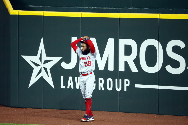 Los Angeles Angels right fielder Jo Adell puts his hands on his head after a fly ball by the Texas Rangers' Nick Solak popped out of his glove and over the right field wall for a solo home run on Sunday. (AP/Ray Carlin)