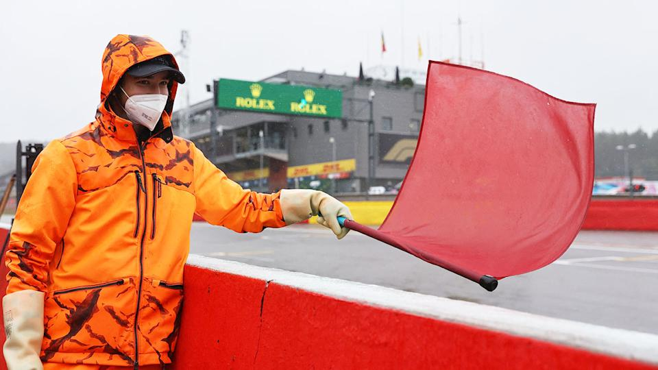 Seen here, a race steward holds up a red flag during the rain-affected Belgian GP.