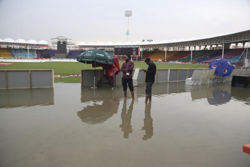 Officials stand at the National Stadium after rain in Karachi, Pakistan, Friday, Sept. 27, 219. Heavy rain has delayed the start of the first one-day international between Pakistan and Sri Lanka. An unusual spell of rain in the southern port city of Karachi during this time of the year left the cricket ground completely waterlogged on Friday. (AP Photo/Fareed Khan)