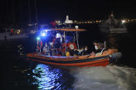 People are evacuated by boat after wildfires reached the Kemerkoy Power Plant, a coal-fueled power plant, in Milas in southwest Turkey, late Wednesday, Aug. 4, 2021. (AP Photo/Cem Tekkesoglu)